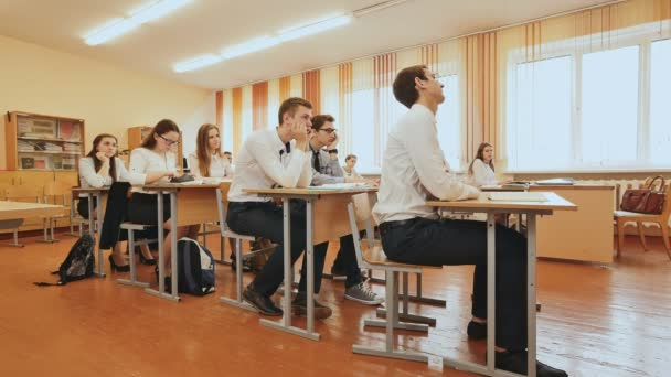 Diákok az osztálytermekben is ülnek az íróasztal mögött. Orosz iskola.