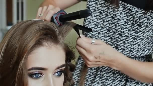 Professional hairdresser using curling iron for hair curls at salon