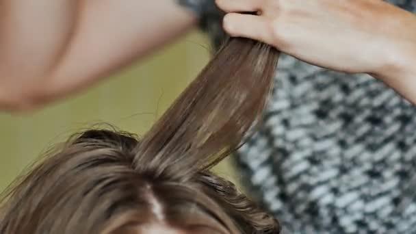 Hair hajsütővas segítségével profi fodrász szalonban fürtök. A fodrász, hogy loknikat barna nő. Fodrász fodrászat haj gyönyörű nő dolgozik. Zár megjelöl kilátás