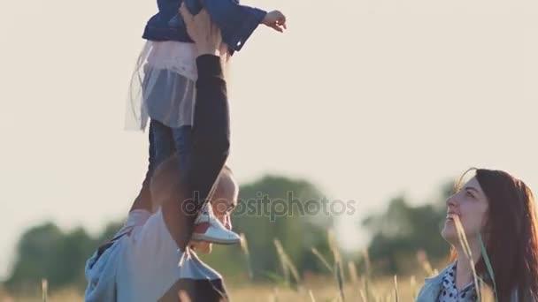 Mladá rodina tří lidí spolu v oblasti pšenice mezi zelené klásky. Malá dcera sedí na ramenou papeže. Společně mají radost příroda v létě. Rodiče hrají s