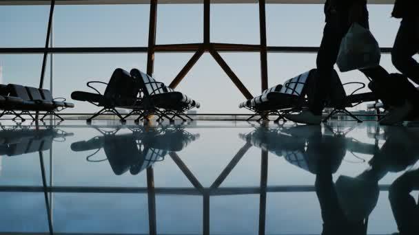 Silueta skupina cestujících s zavazadla na letišti