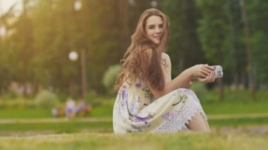 Young beautiful woman in summer dress with long hair sitting on grass in green park and talking on the phone, smiling. Summer. Recreation. Youth.
