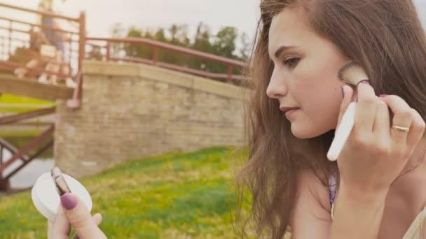 Krásná a udržovaná dívka s dlouhými vlasy v parku v přírodě. Ona používá prášek prášek její tváře. V létě. Krása