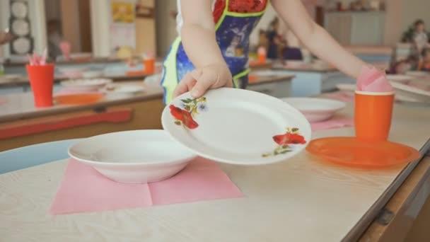 Jídelní stoly s talíře, hrnky, vidličky a lžíce ve školce. Příprava pro přestávku na oběd od malé holčičky. Položila desky na stůl