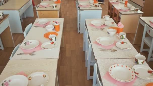 Jídelní stoly s talíře, hrnky, vidličky a lžíce ve školce. Příprava na oběd. Prostřený stůl