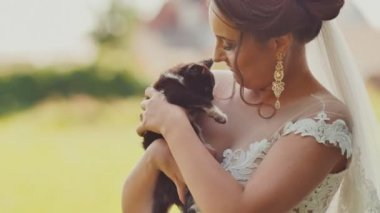 The charming brunette bride is touchingly holding a small kitten in her arms. The moment of the wedding day.