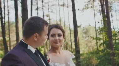 An elegant groom and a charming bride with a bright bouquet, walking along a forest trail among the pines. A happy moment of the wedding day.
