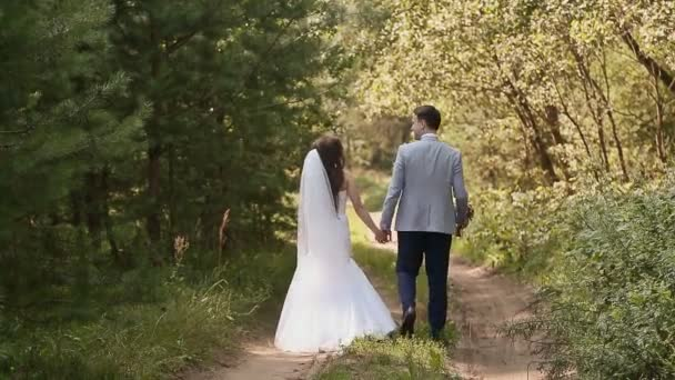 9a179797ca Novia de vestido blanco y el novio en el bosque. Juntos caminan manos de  explotación. Feliz junto. Día de la boda– metraje de stock