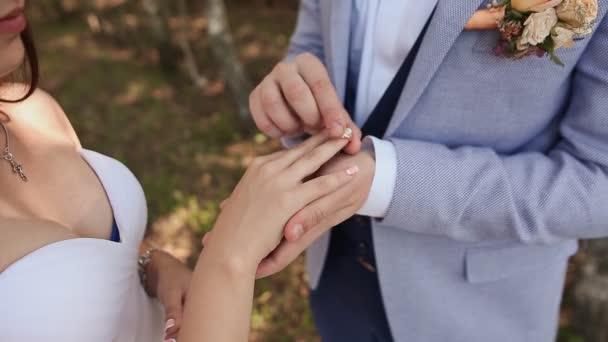 La sposa e lo sposo scambio di fedi nuziali contro una priorità bassa di verde della natura. Lo sposo mette lanello sul braccio del suo primo piano sposa. Giorno del matrimonio