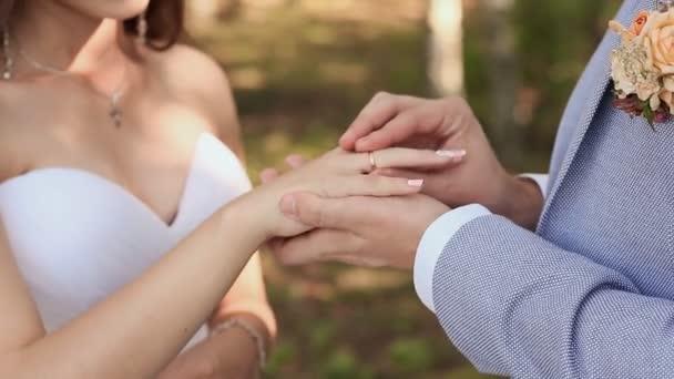 Nevěsta a ženich vyměnit snubní prsteny na pozadí zelené přírody. Ženich dává prsten na rameni jeho nevěsta detail. Svatební den