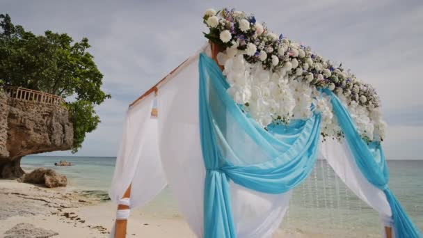 A wedding arch decorated with flowers and large wind developing a wedding arch decorated with flowers and large wind developing fabrics on a tropical beach junglespirit Image collections