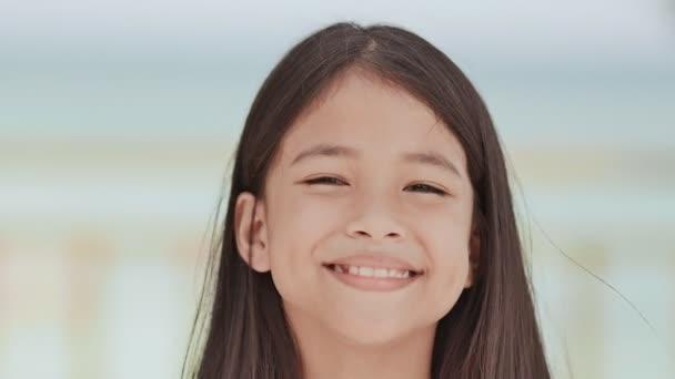 Okouzlující filipínský školačka, představuje pozitivně. Detail tváře na bílo modré pozadí tropické pláže