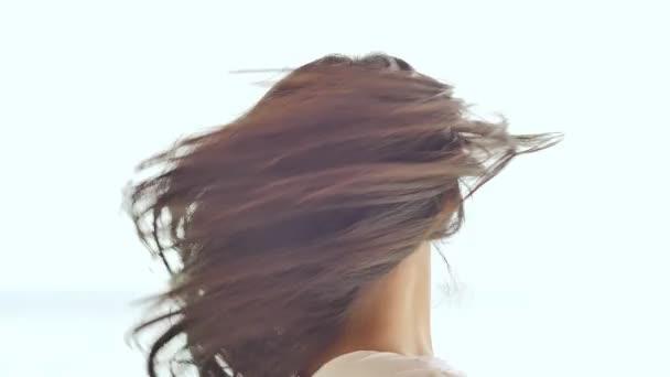 Okouzlující filipínská školačka radostně představuje, rotující její vlasy. Detail tváře na bílém pozadí letní přírody