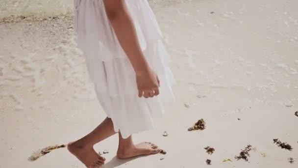 Nahé a opálené nohy filipínská školačka v bílých šatech chodit na bílý písek, dojemné pěnivý vlny u pobřeží. Luxusné. Dětství