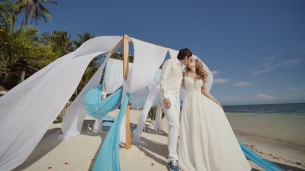 Svatební pár na tropické pláži u oceánu. Polibek pod obloukem s křídly bílé a modré vzduchu létal ve větru. Okolo konfety - okvětní lístky rudých růží. Happy dohromady.