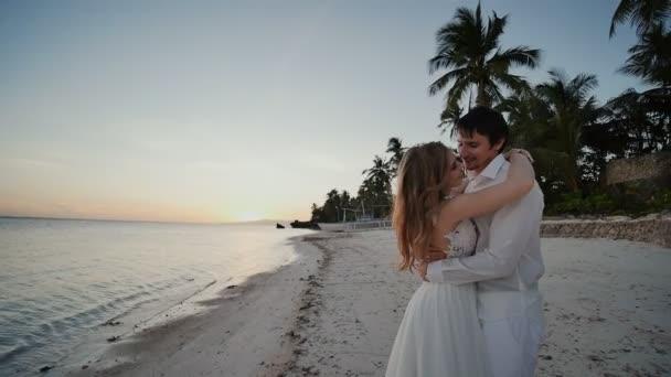 Die Braut und Bräutigam durch den Ozean. Küsse bei Sonnenuntergang an einem wunderschönen tropischen Strand mit Palmen. Romantische Ehepaar. Sinnliche Umarmung. Unglaublich schönen Sonnenuntergang