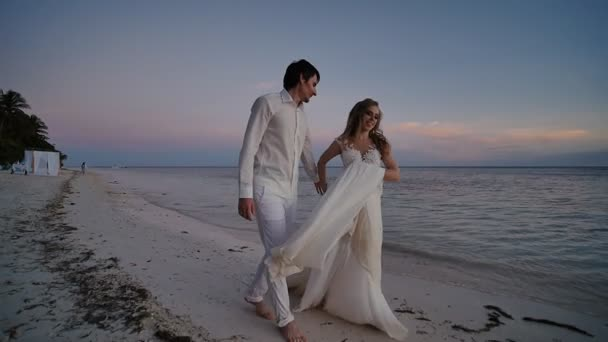 The bride and groom at sunset on a beautiful tropical beach. The bride sensually dances before the groom, holding on to the dress and turning. They are barefoot on the sandy shore of the ocean