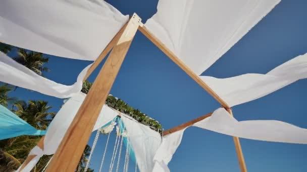 Svatební oblouk zdobí květinami a velkým větrem rozvoj tkaniny na tropické pláži. Filipíny. Bohol