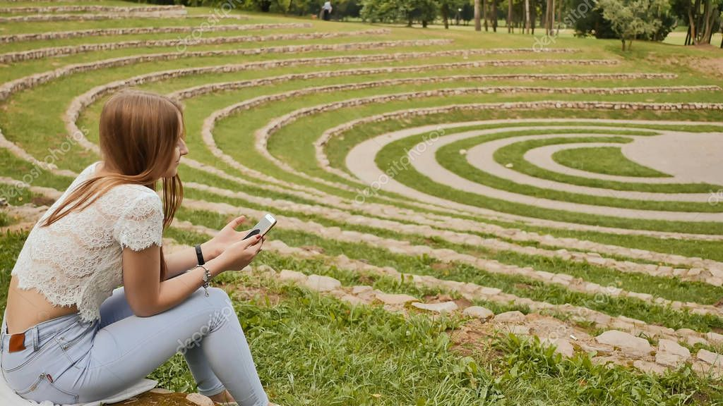 A young female student sits at the edge of the stadium on the grass and holds a mobile phone in her hands. Rest during study.