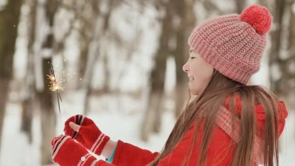 Šťastná mladá školačka s šumivé jiskry z Bengálska světla mezi zimní les. V předvečer nového roku prázdnin