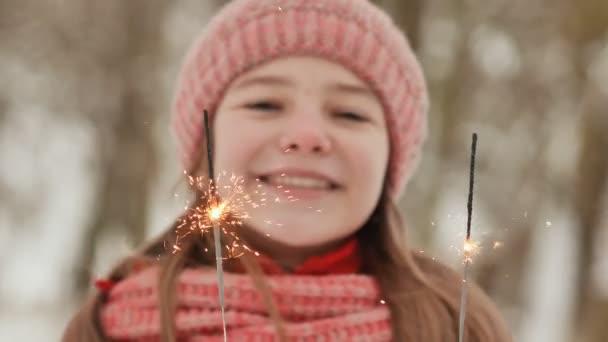 Šťastná mladá školačka s šumivé jiskry z Bengálska světla mezi zimní les. Detail obličeje. V předvečer nového roku prázdnin