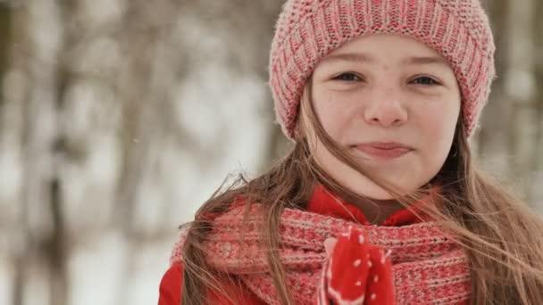 Portrét mladé školačky s pihy v lese v zimě. Hřeje ruce v palčáky a aplikuje je na jeho tvář a rty. Ruku v ruce se zobrazí pohyb.