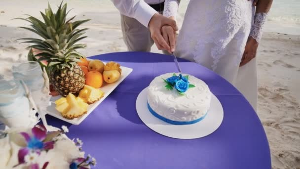 The bride and groom together cut the wedding cake on a sandy sea beach. A fascinating moment. A tropical Philippine wedding.