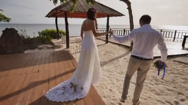 The bride and groom walk together holding hands on the hotels terrace overlooking the ocean. From the height of the balcony they depict the flight of love. Wedding day. Philippine Tropics.