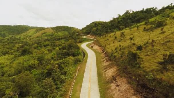 Dlouhé a klikaté cestě procházející zelenými kopci. Busuanga ostrov. Coron. Letecký pohled. Filipíny