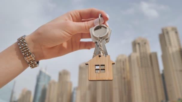 Das Konzept des Kaufs einer Wohnung in Dubai Wolkenkratzern. Das Mädchen hält die Schlüssel für eine neue Wohnung in der Hand.