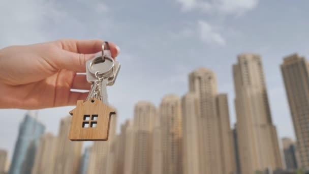 Das Konzept, eine Wohnung in den Wolkenkratzern einer Großstadt zu kaufen. Mädchen hält Schlüssel für ein neues Zuhause.