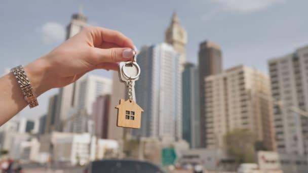 Koncept koupě bytu v dubajských mrakodrapech. Dívka drží v ruce klíče od nového bytu.