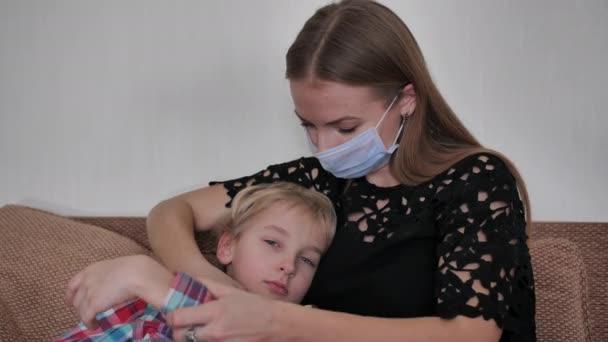 Eine fürsorgliche Mutter im Verband misst die Temperatur ihres Sohnes.