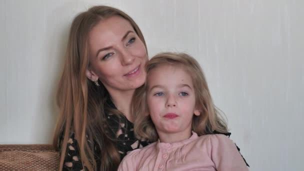 Matka s dcerou sedí doma na gauči.
