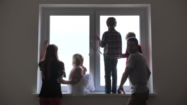 Silhouette of a large family on the background of a window in a new apartment.