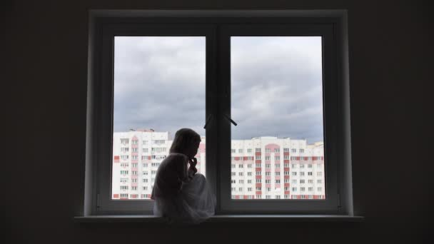 Osamělé dítě dívka sedí na parapetu u okna v apartmánech.