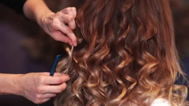Dívka kadeřník dělá účes v podobě spinning vlasy.