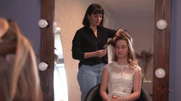 Lány fodrász csinál frizura formájában forgó haj.