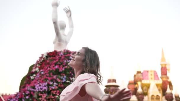 Dívka se těší v květinovém parku města Dubaj.