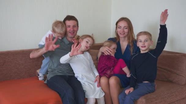 Egy nagy, barátságos család a kanapén integet és pózol az otthonukban..
