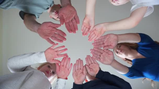A friendly large family makes a circle shape out of the palms of their hands.