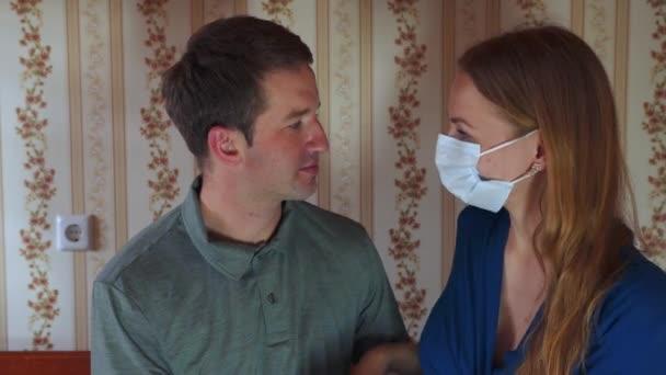 Domácí karanténa. Manželé se doma líbají a schovávají se za maskou.
