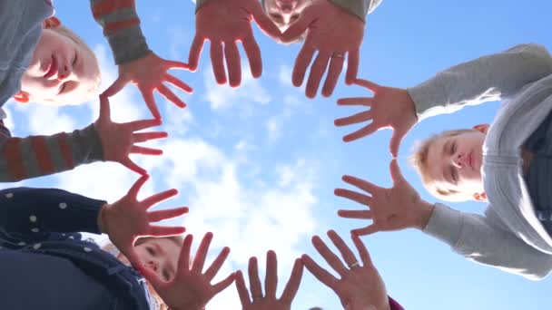 Eine freundliche Großfamilie formt aus ihren Handflächen einen Kreis.