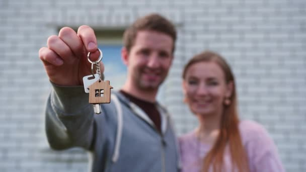 Real estate purchase concept. Young spouses show off keys to the purchased new home.