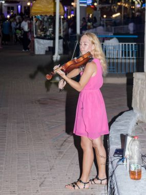 The young girl in the summer evening plays for passers-by on the violin on the waterfront of Nahariya, Israel
