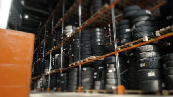 Auto pneumatiky ve skladu v obchodě pneumatiky. Obrovský sklad pneumatik, uložených na policích