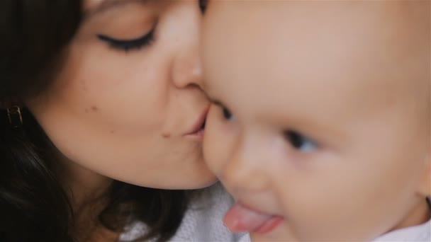 Young Happy Mother Holding her Newborn Child and kissing. Family at home. Beautiful smiling Mom and Happy Baby Together. Tenderness concept.