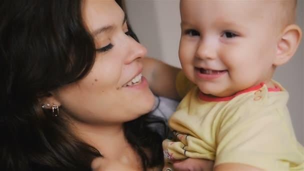 Šťastná maminka drží své novorozené dítě. Rodina doma. Krásná maminka a Happy Baby dohromady