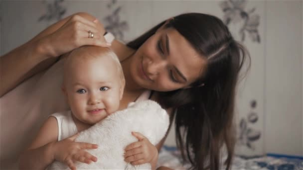 Young beautiful woman hugging her cute daughter with toy in berroom - motherhood concept