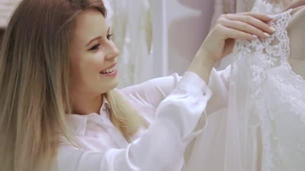 Ženské obchod konzultant pomáhá nevěstě vybírá šaty v obchodě svatební módy. Zaměřit se na dívky